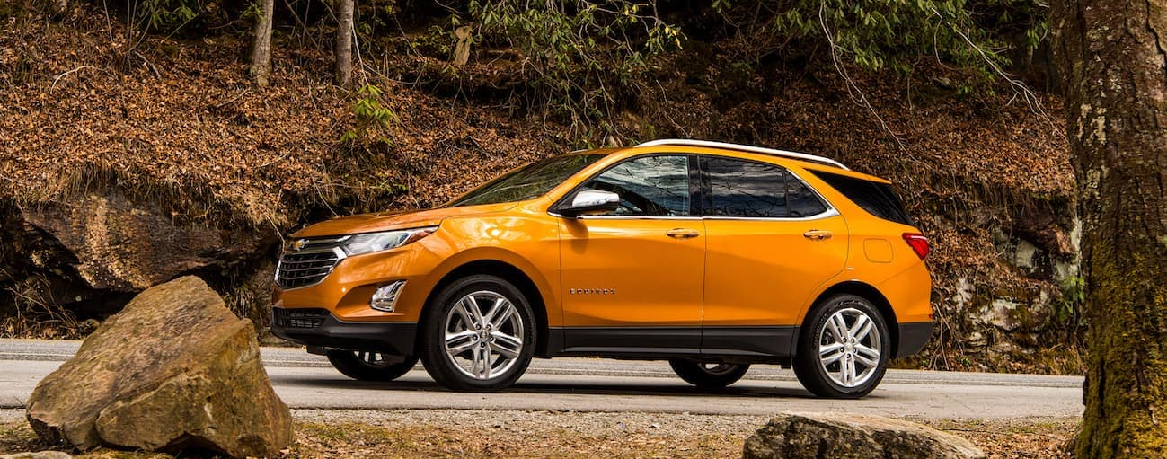 An orange 2018 Chevy Equinox, which wins when comparing the 2018 Chevy Equinox vs 2018 Nissan Rogue, is driving on a near Cincinnati, OH road with trees in the background.