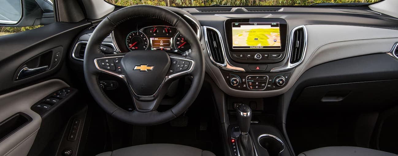 The black and grey leather interior of a 2018 Chevrolet Equinox is shown with a touchscreen.