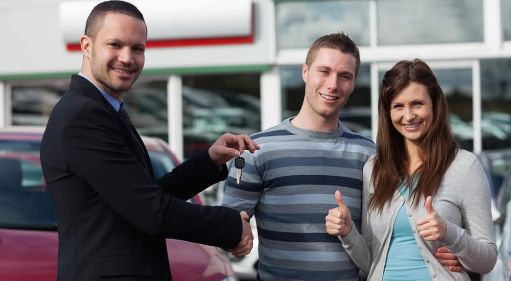 Dealer shaking hand of a man while giving him car keys in a dealership