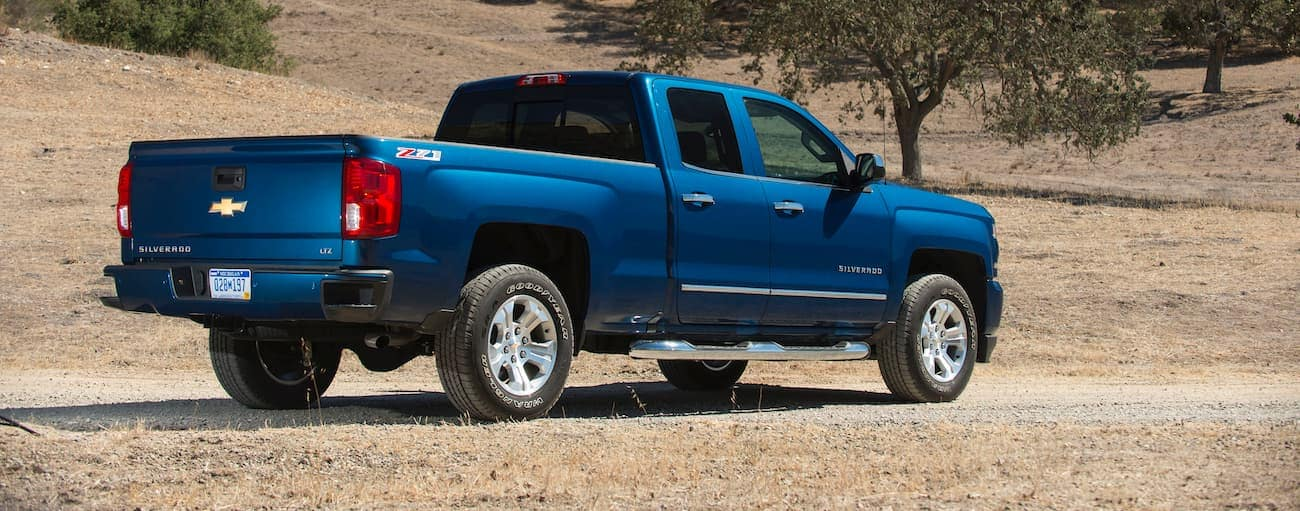 A blue 2018 Chevrolet Silverado is shown from the rear on a dirt road.
