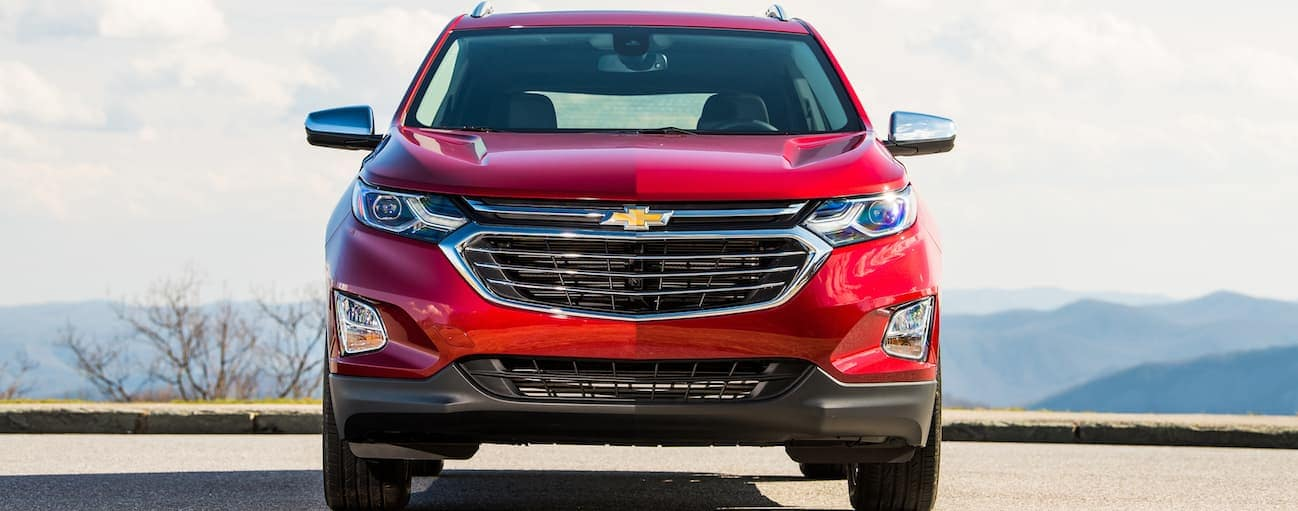 A red Chevy Equinox is parked in an empty parking lot on a sunny day.