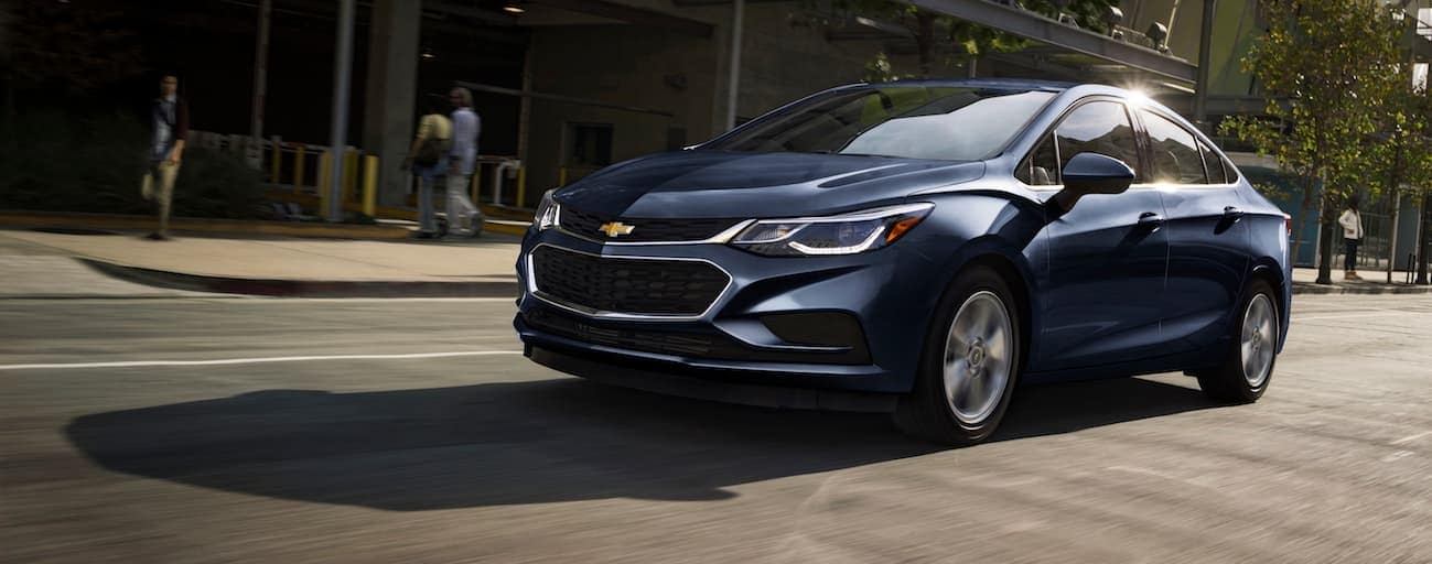 A blue 2018 Chevy Cruze, which wins when comparing the 2018 Chevrolet Cruze vs 2018 Ford Focus, is driving through a city near Cincinnati, OH.