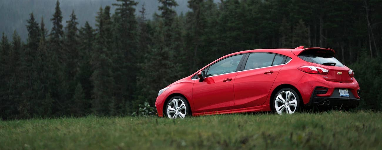 A red 2018 Chevy Cruze hatchback is parked near a wooded area.