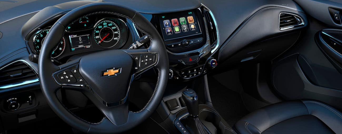 The front black leather interior is shown with a touchscreen and other high tech features.