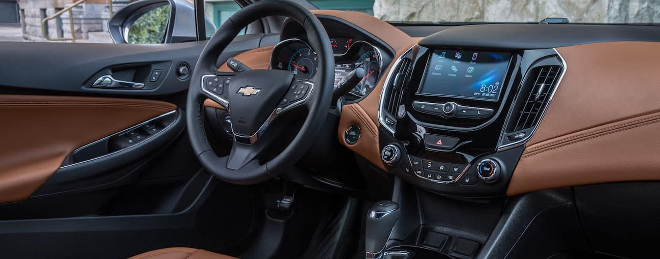 The front brown and black leather interior of a 2018 Chevy Cruze is shown with a touchscreen.