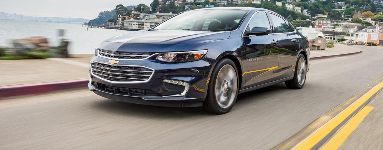 A dark blue 2018 Chevy Malibu is driving down a road next to a lake.
