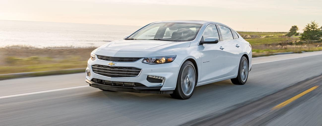 A white 2018 Chevy Malibu is driving passed water on a sunny day.