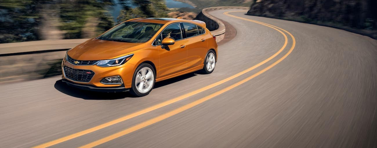 An orange 2018 Chevy Cruze hatchback is driving on a highway next to a lake.