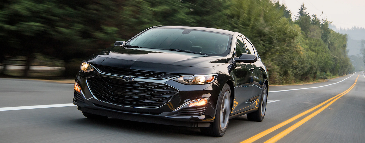 A black 2019 Chevrolet Malibu is driving on a tree-lined road outside of Cincinnati, OH.
