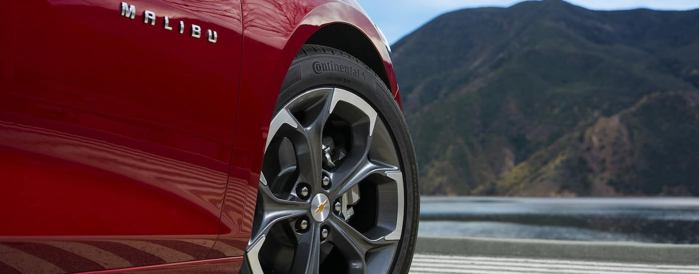 A red 2019 Chevrolet Malibu is parked in front of a mountain lake, with a close up on the wheel.