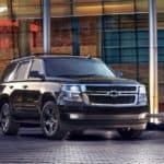 A Black Chevy Tahoe in front of a glass building