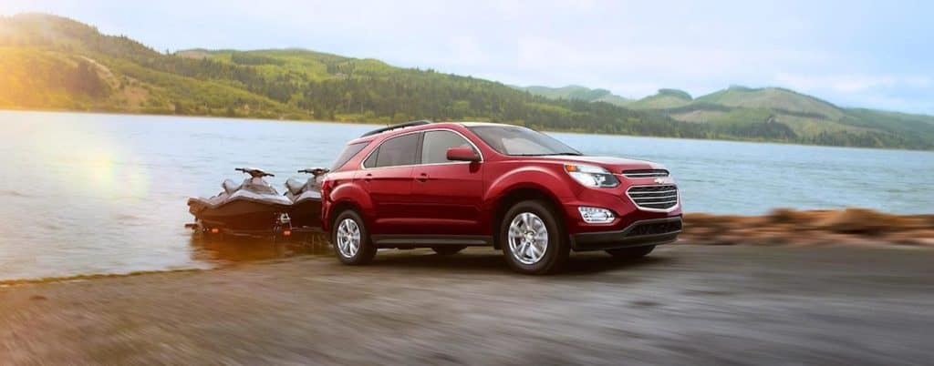 A red Chevy Traverse pulls jets skis out of a lake