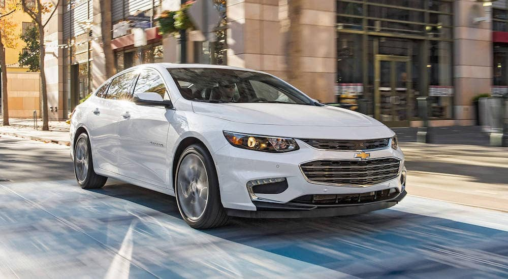 A white 2017 Chevy Malibu drives down a small city street in Ohio