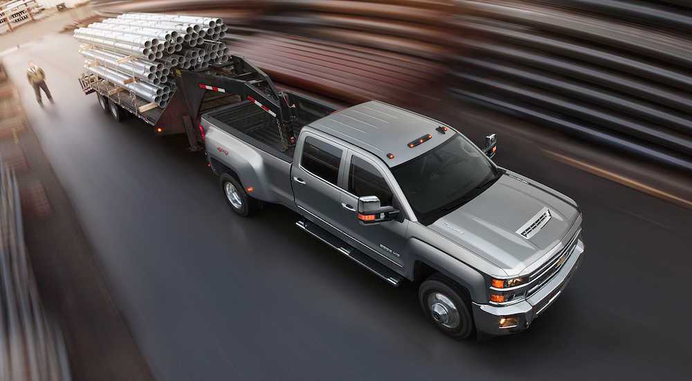 Silver 2018 Chevy Silverado 3500 hauling a trailer of pipes