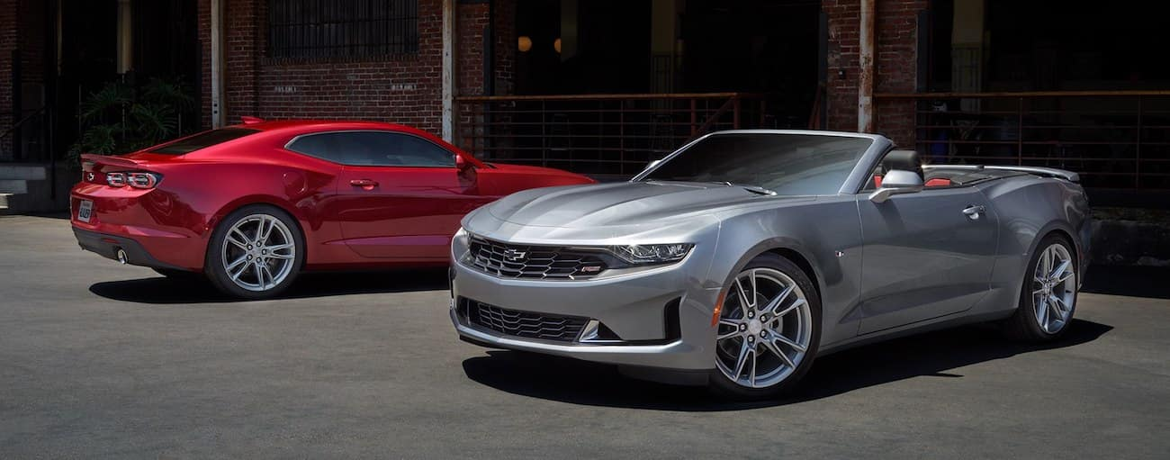 Red 2019 Chevy Camaro sedan and grey convertible in front of brick building