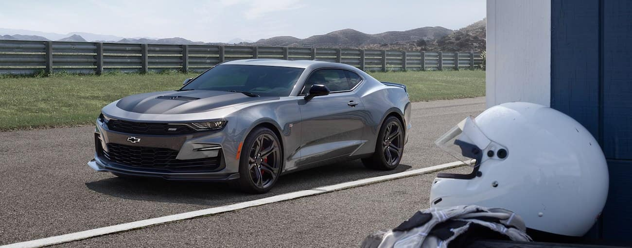 Silver 2019 Chevy Camaro on race track, helmet in foreground