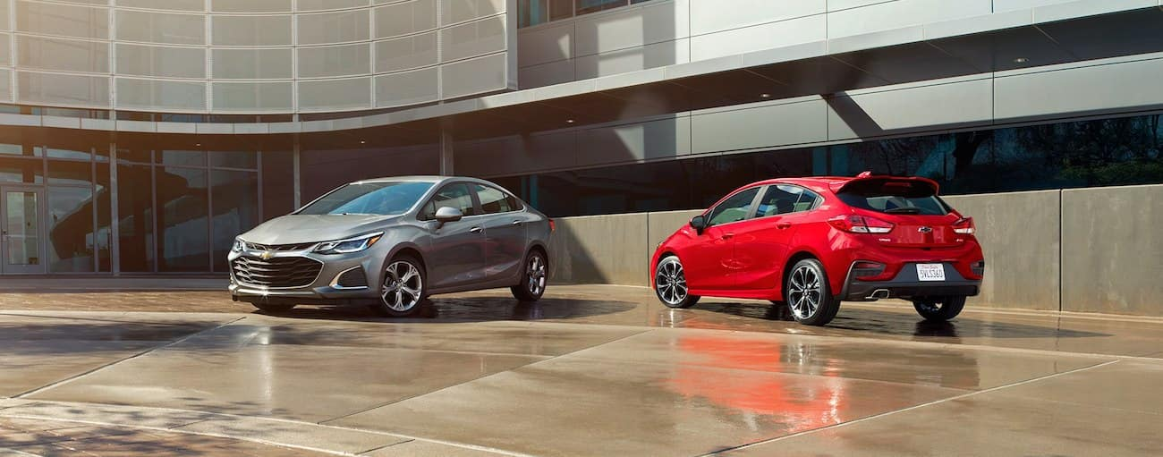 Gray 2019 Chevy Cruze sedan and red hatchback in front of office building