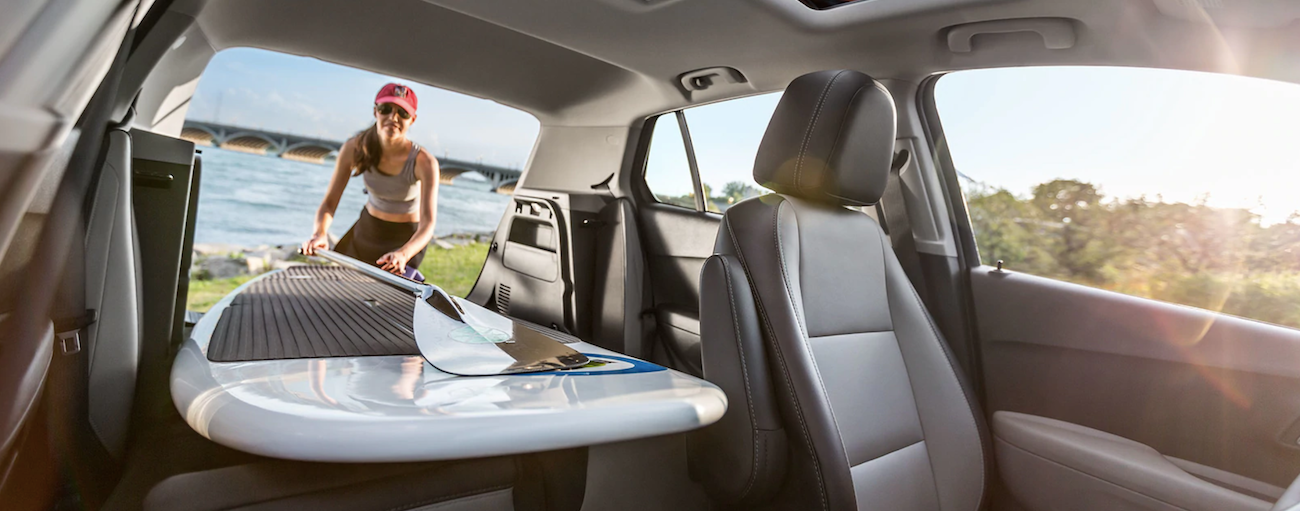 Woman loading paddle board into a 2019 Chevy Trax