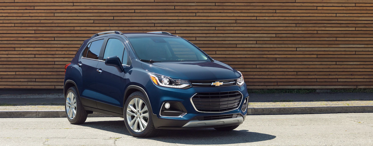 Blue 2019 Chevy Trax in front of wooden wall