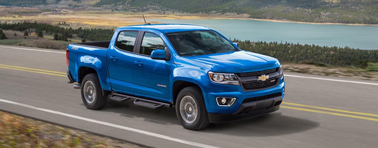 Blue 2019 Chevy Colorado driving in front of lake