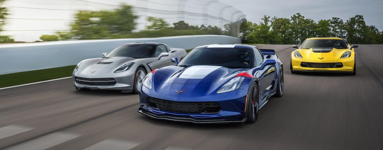 3 2019 Chevy Corvettes on a racetrack, silver stingray, blue grand sport, yellow z06