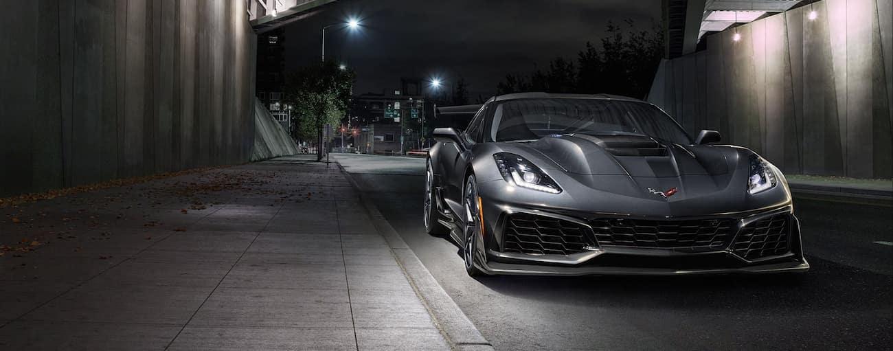 Gray 2019 Chevy Corvette zr1 under bridge at night