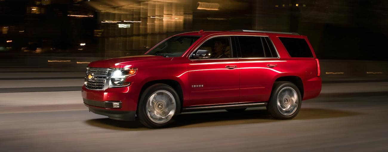 Red 2019 Chevy Tahoe driving on city street at night