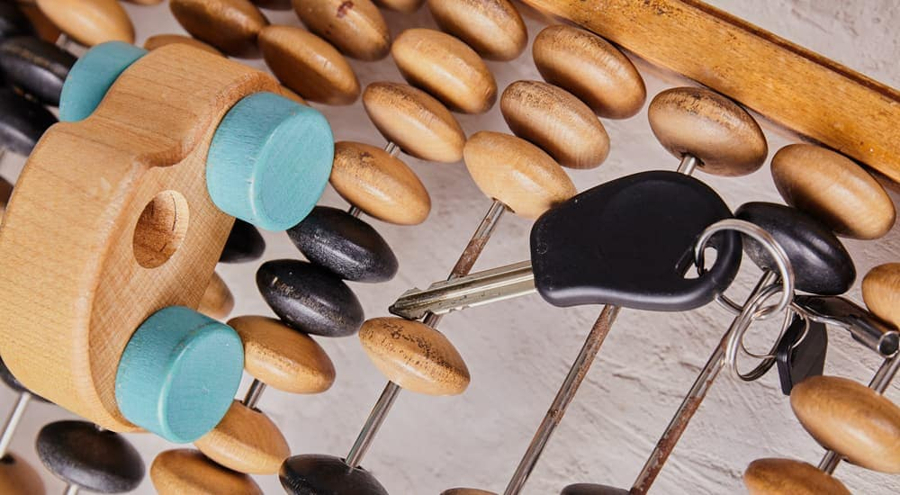 Wooden toy car and car keys on an abacus
