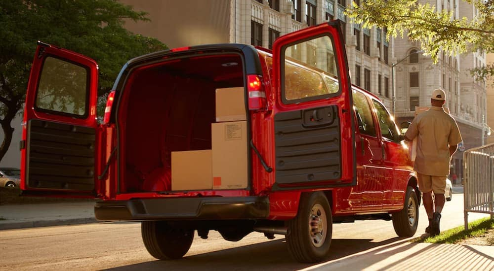 Red Chevy Express Cargo van full of boxes in city
