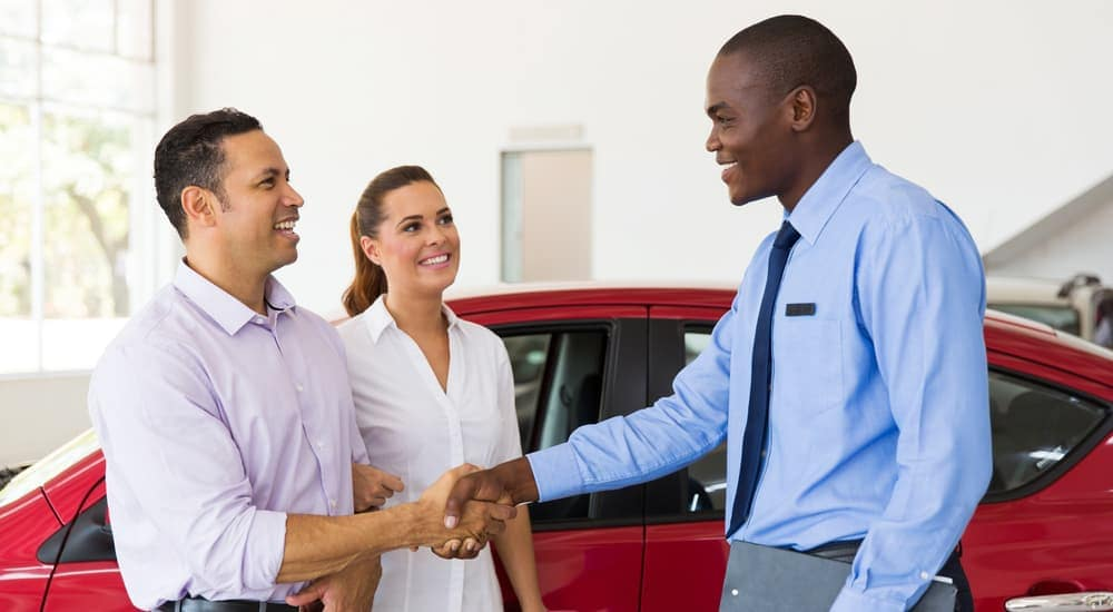 Couple shaking hands of car salesman, red car in back
