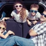 Man and 3 kids in back of silver car