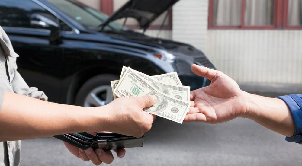 Man handing cash to another person, car in back with hood open