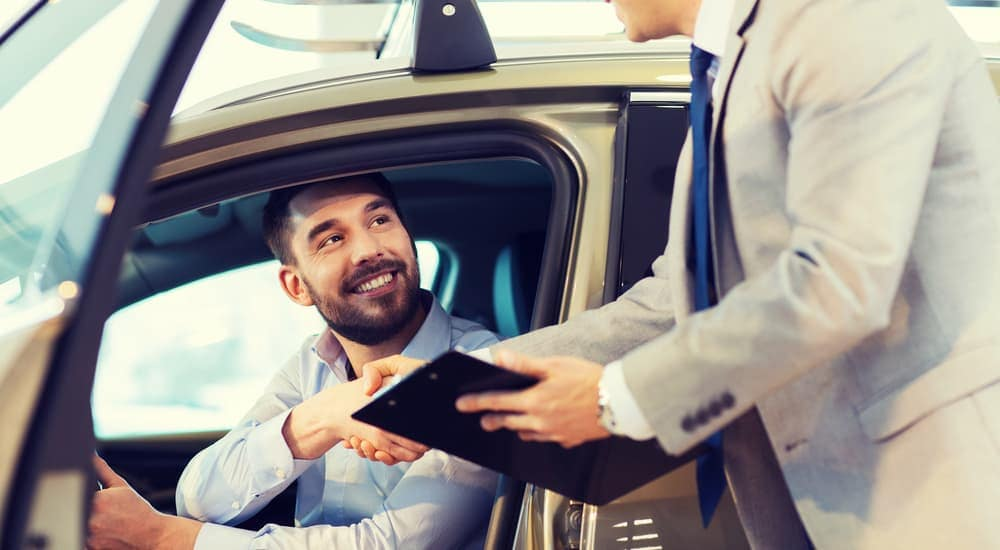 Man sitting in car shaking hands with salesman