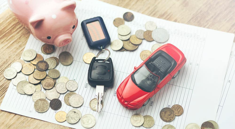 Papers, coins, piggy bank, car keys and toy car sitting on table