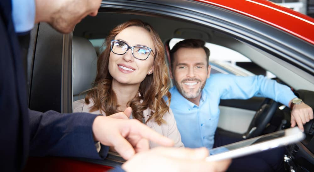 Couple in car being shown tablet by salesman