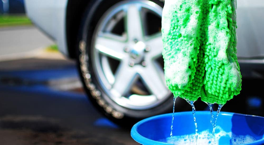 Soapy green rag and bucket of water for washing car, tire in back