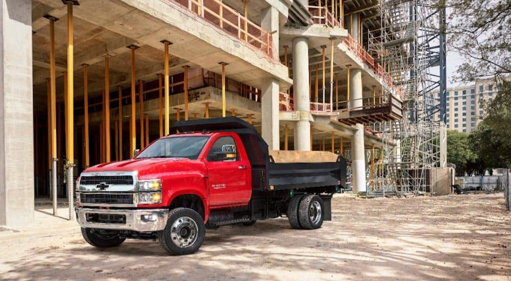 A bight red Chevy commercial truck with black dump body is parked at a job site in Cincinnati.
