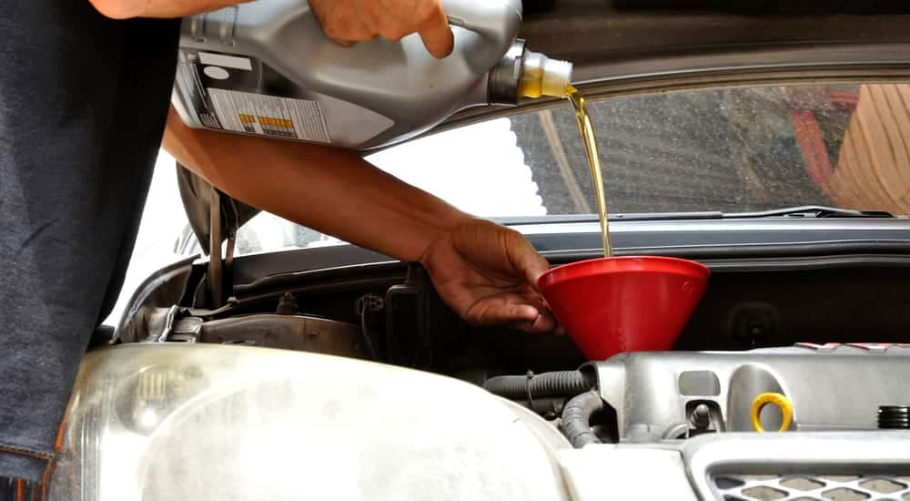 Oil being poured into a car during a quick oil change at McCluskey Chevy