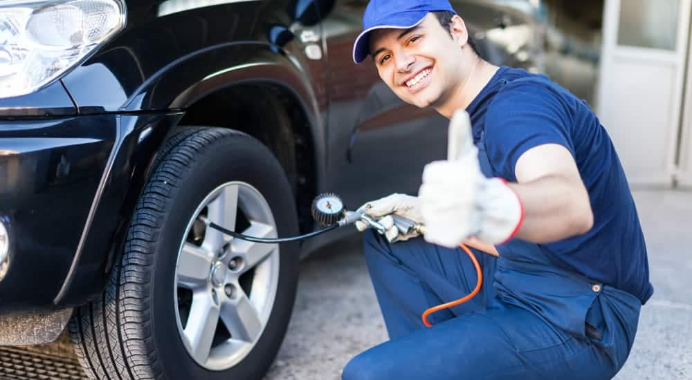 A tech at McCluskey Chevy checks tire pressure during a quick oil change