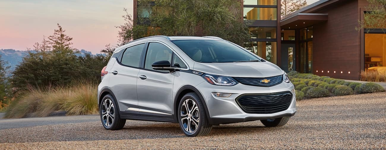 A silver 2019 Chevy Bolt outside an upscale modern home