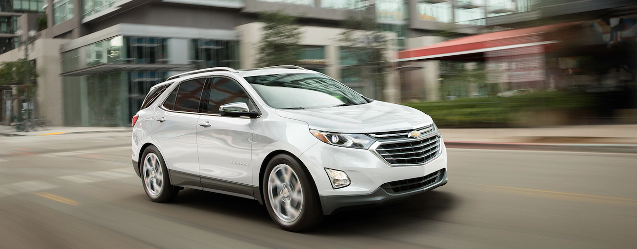 A white 2019 Chevy Equinox travels an empty city street