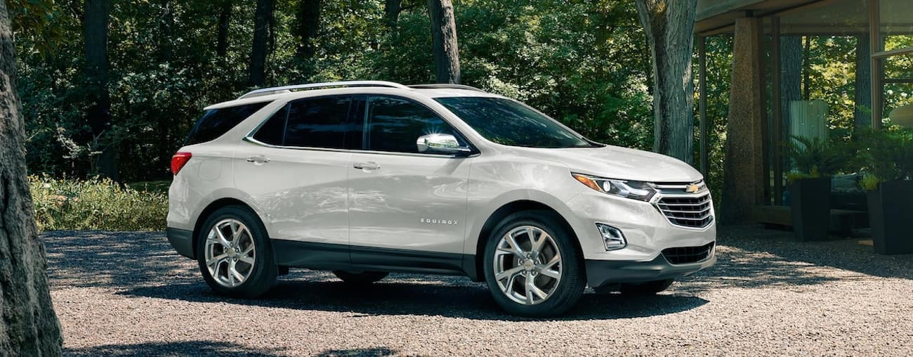 A white 2019 Chevy Equinox parked in a tree lined driveway