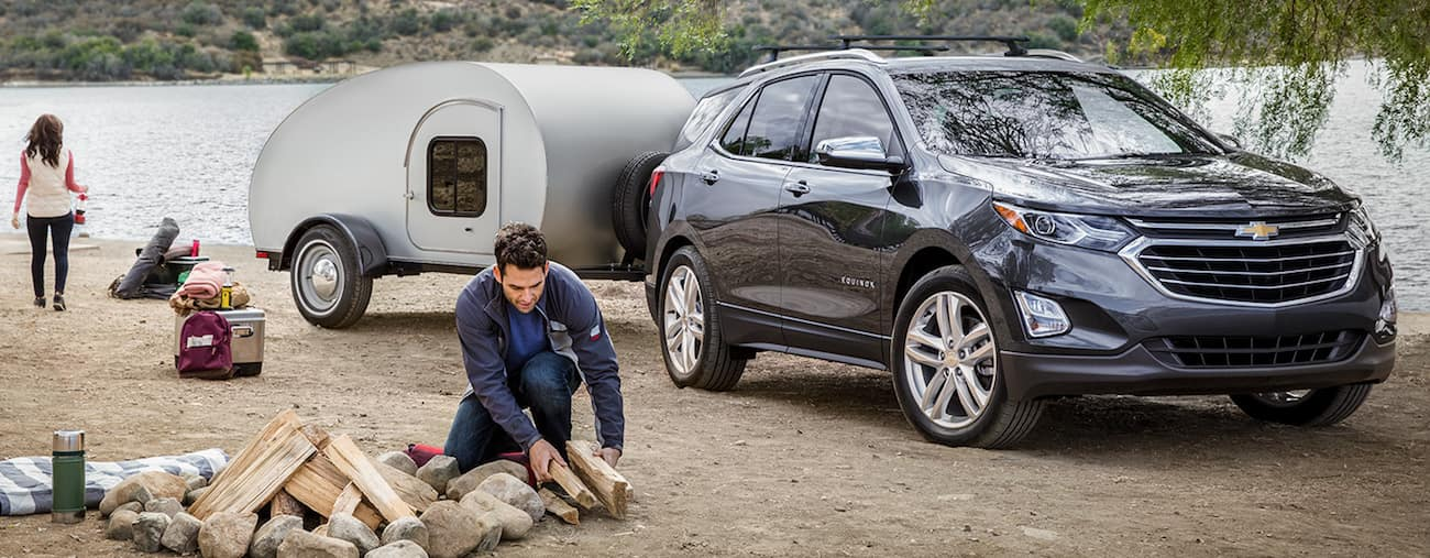A blue 2019 Chevy Equinox towing a camper on a family camping trip