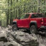 A red 2019 Chevy colorado, one of the most popular Chevy trucks for sale, navigates a rocky trail