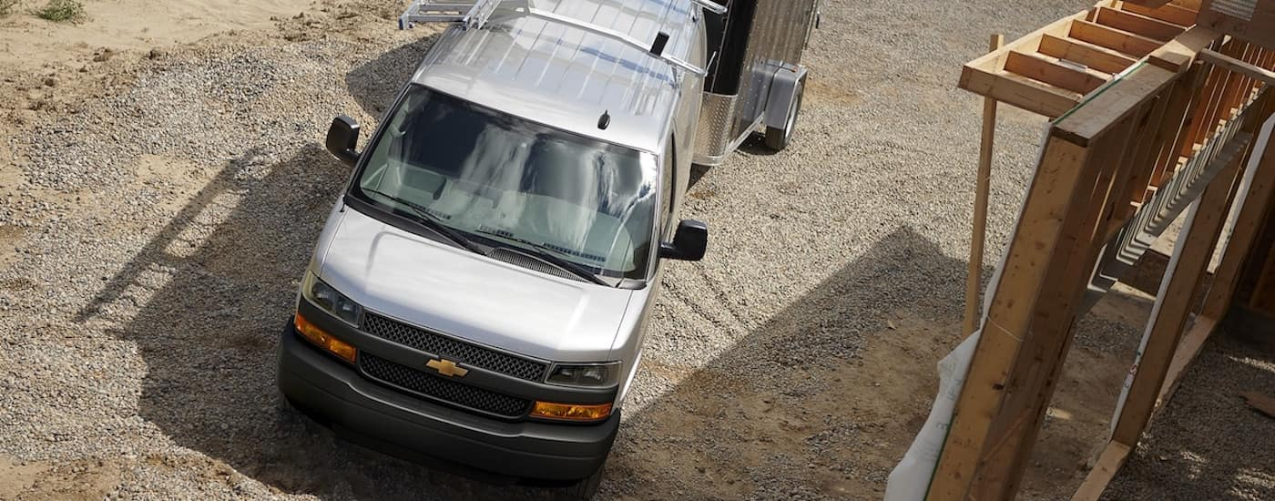 A silver 2019 Chevy Express Van is shown from above at a construction site towing an enclosed trailer. One of many Chevy vans for sale that can tow large trailers