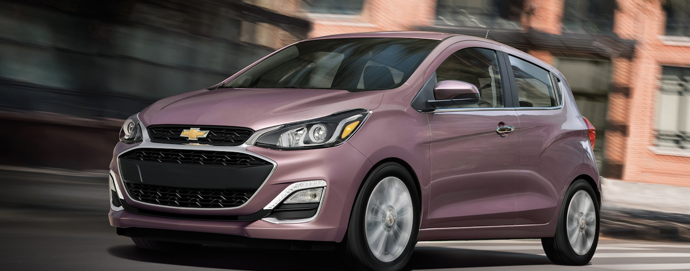 A pink 2019 Chevy Spark Driving in a city