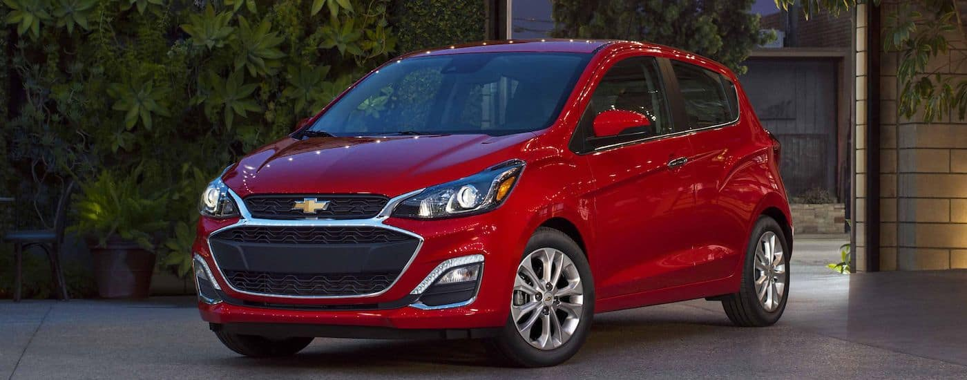 Red 2019 Chevy Spark in yard with plant covered wall in back