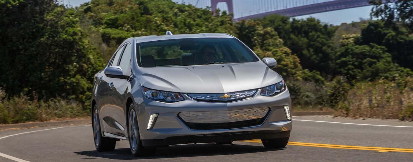 Silver 2019 Chevy Volt Driving with bridge in back