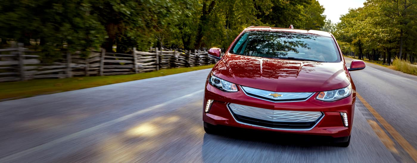 Red 2019 Chevy Volt Driving on wooded road towards camera