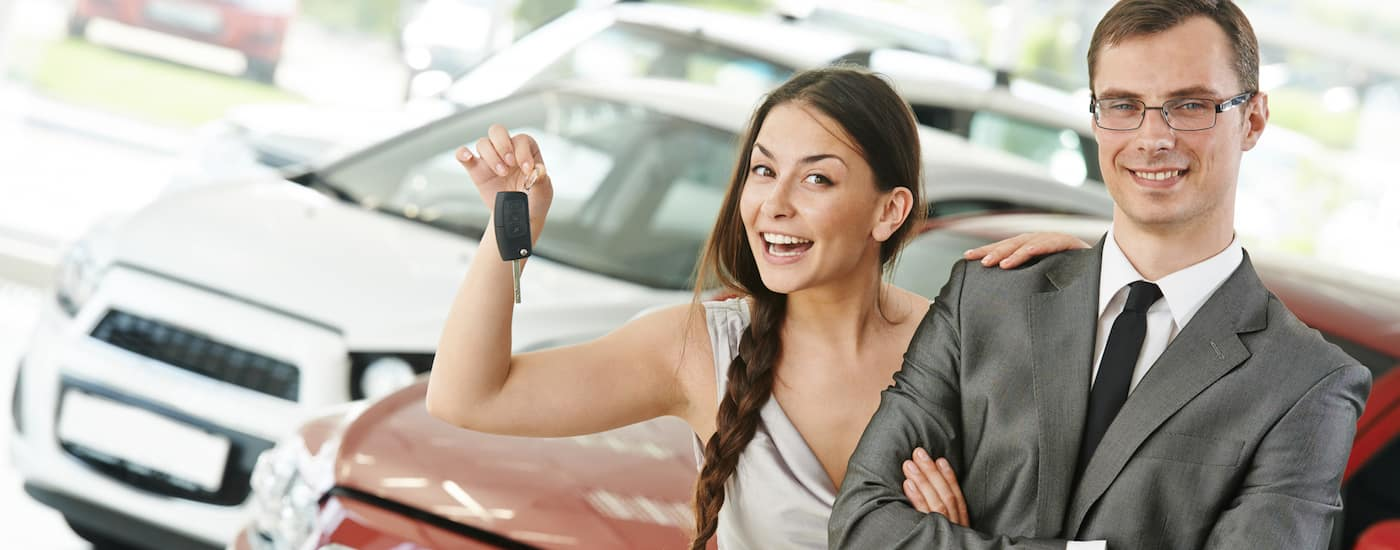 A young lady with the keys to her new car is shown with a salesman after getting a great trade in value for her old car.